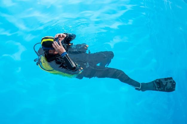 스쿠버 다이버는 수영장에서 그의 등에 수영