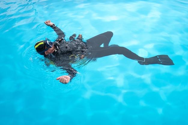 Аквалангист плавает на спине в бассейне