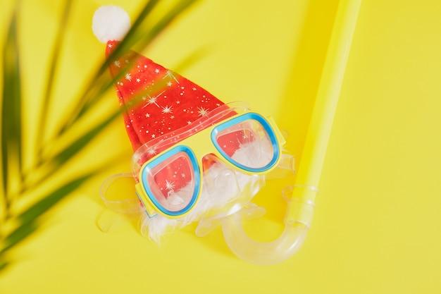 Набор для подводного плавания, шляпа санта-клауса и пальмовый лист на желтом фоне, рождественские каникулы на пляже в теплой стране