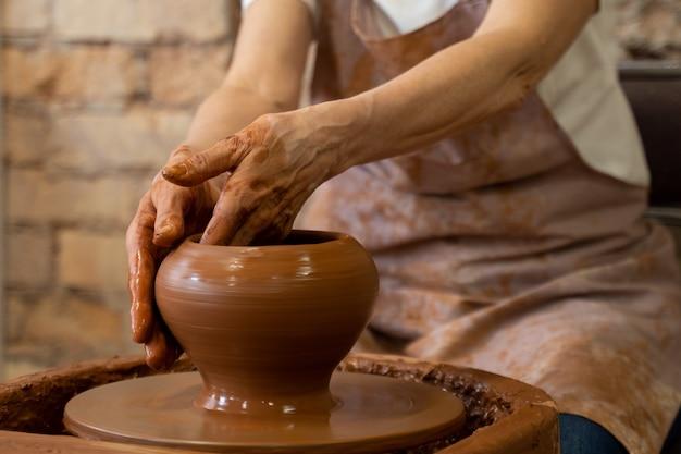 スタジオの彫刻家が土鍋のクローズアップを作成します年配の女性が回転するろくろの後ろにボウルを彫刻しています
