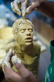 Sculptor making human body model with clay