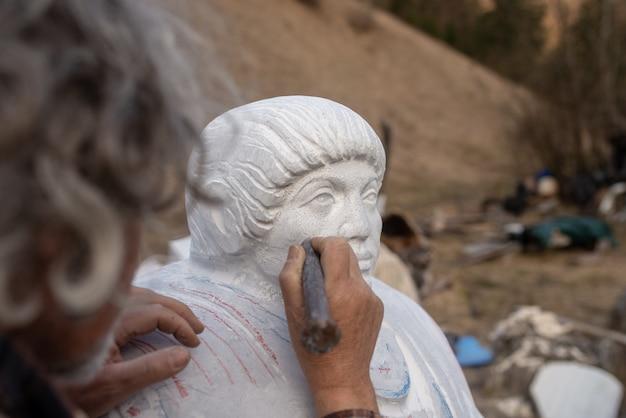 Скульптор работает над своей статуей, используя долото для обработки деталей.