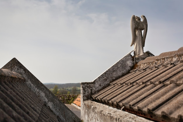 Sculpture of the guardian angel on the roofs of the pantheons in a cemetery religious concept