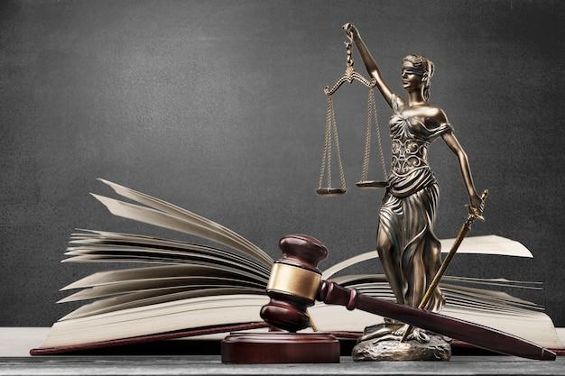 正義のブロンズの女性を彫刻し、本と小槌を開く