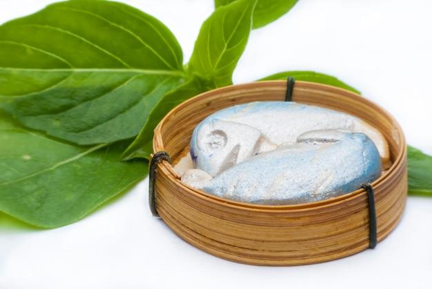 Скульптура рыбы скумбрия в бамбуковой корзине на белом фоне