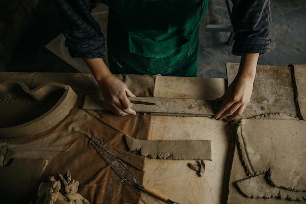 粘土片にスケッチを作る彫刻