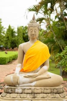 Скульптура будды в желтом одеянии во время медитации в ают