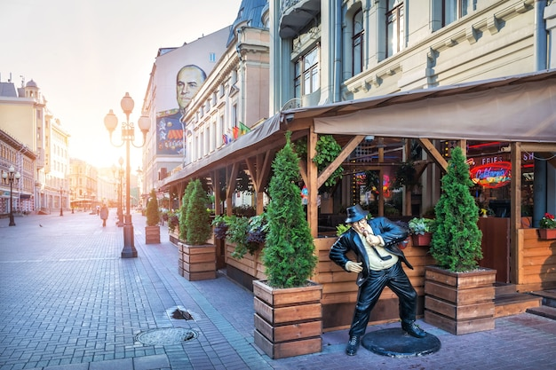 A sculpture of a singer at the veranda of a cafe on the arbat in moscow on a summer morning