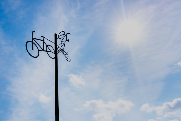 Sculpture with bicycle silhouettes hanging on a pole, with sky and sun in the background.