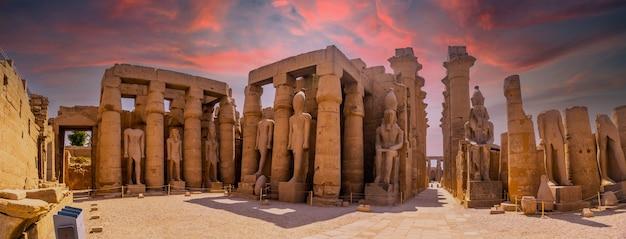 Скульптуры древнеегипетских фараонов и рисунки на колоннах луксорского храма вечером. египет