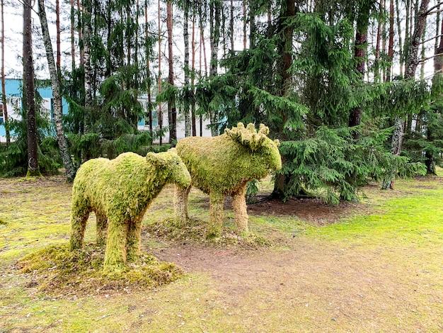 Скульптуры животных в лесу из природных материалов Premium Фотографии
