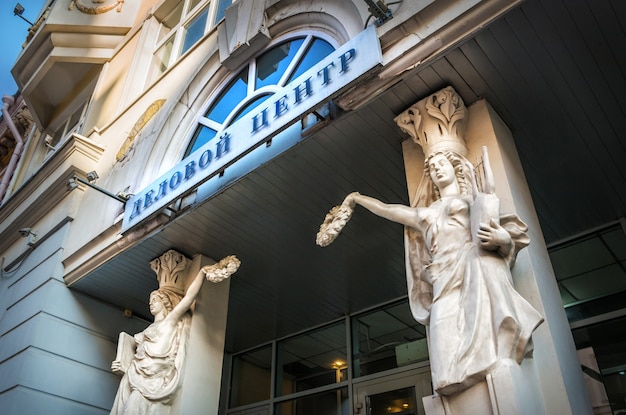 Sculptures of women on the facade of the business center on arbat street in moscow caption: business center
