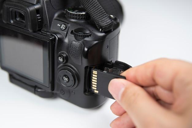 Sdメモリカードを持っている写真家の手は、dslrカメラを挿入します。