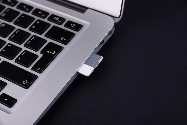 黒い背景にラップトップに挿入されたsdフラッシュドライブ