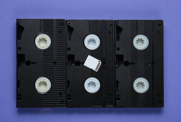 Sd memory card, video cassette on purple paper with geometric shapes