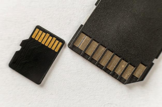 マイクロsdメモリカードと白いコピースペース背景に分離されたsdアダプターのクローズアップ。現代の技術コンセプト。