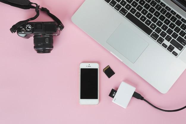 カメラとピンクのテーブルの上のsdカードとノートパソコン