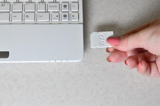 女性の手が白いコンパクトなsdカードを対応するものに挿入します