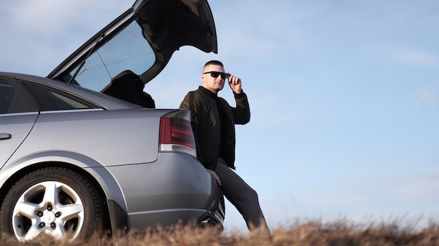 Sde view of young businessman in eyeglasses sitting on car trunk in nature
