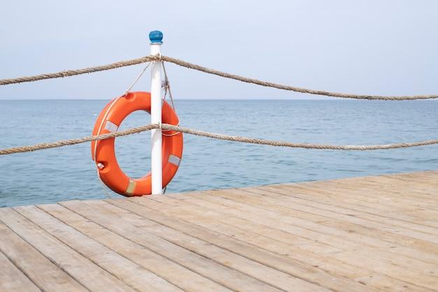 救命浮き輪のある海と桟橋。海のそばで休んでください。