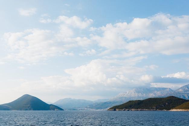 Море и скалистые горы на границе черногории и хорватии белые облака на голубом небе