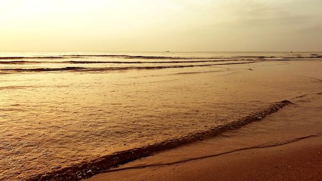 朝の時間にビーチで雲と波と海と空