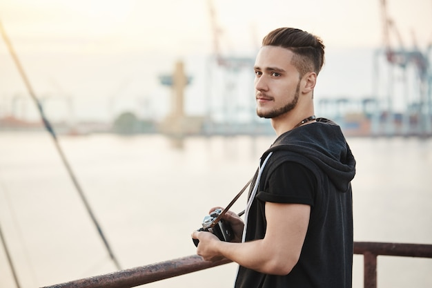 Sea attracts this photographer. outdoor portrait of attractive young guy standing in harbour, enjoying looking at sea while holding camera, searching for good location to take photo, looking aside