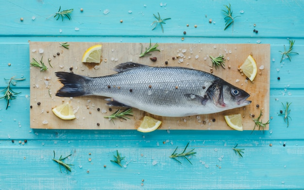 Sea bass on kitchen table on blue wooden background. top view.
