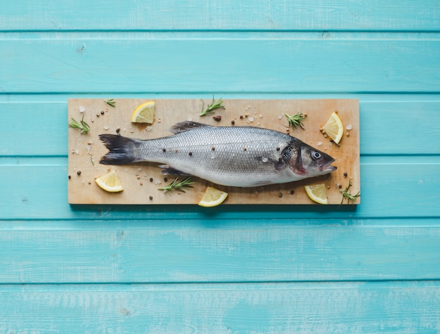 Sea bass on kitchen table on blue wooden background with space to write. top view.