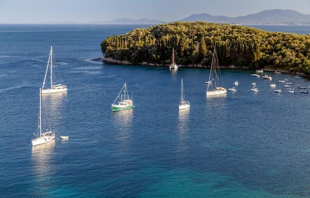 Морская бухта с яхтами и лодками в кристально чистой лазурной воде в палеокастрице, греция