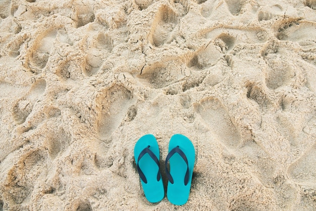 Sea on the beach footprint  people on the sand and slipper of feet in sandals shoes on beach sands, travel holidays concept.