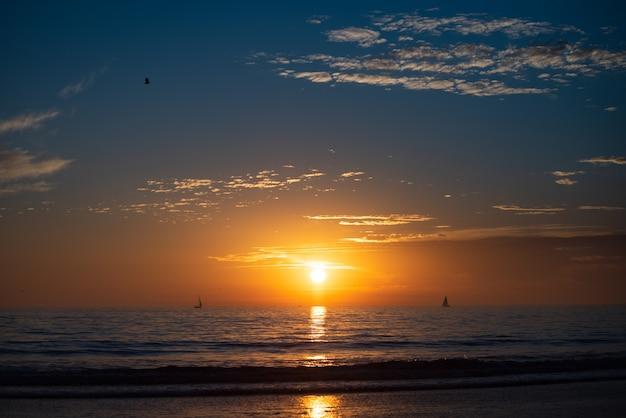 夕焼け空の抽象的な背景と海のビーチ。夏休みと旅行のコンセプトのコピースペース。