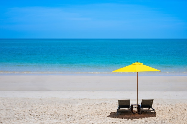 夏の黄色い傘の下に 2 つのラウンジ チェアがある海のビーチ