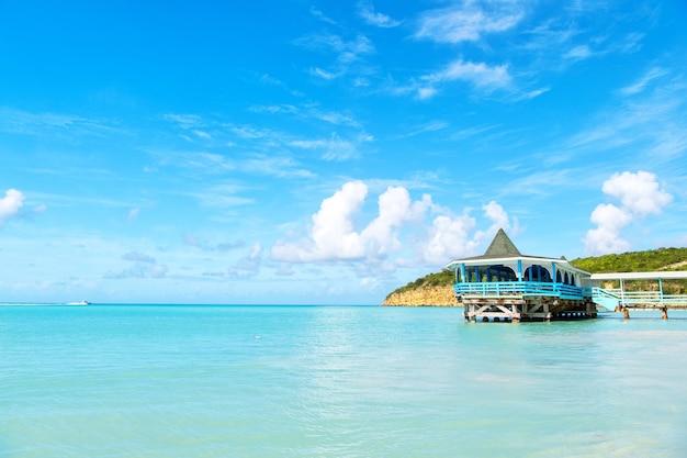 アンティグアの晴れた日に木製の避難所と海のビーチ。青空の背景にターコイズブルーの水の桟橋。カリブ海の夏休み。ワンダーラスト、旅行、旅行。冒険、発見、旅。