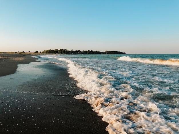 海の青いアクアマリンの波が日当たりの良い砂浜に並んでいます。海の泡の柔らかい波。自然な背景の空