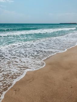 海の青いアクアマリンの波が日当たりの良い砂浜に並んでいます。海の泡の柔らかい波。