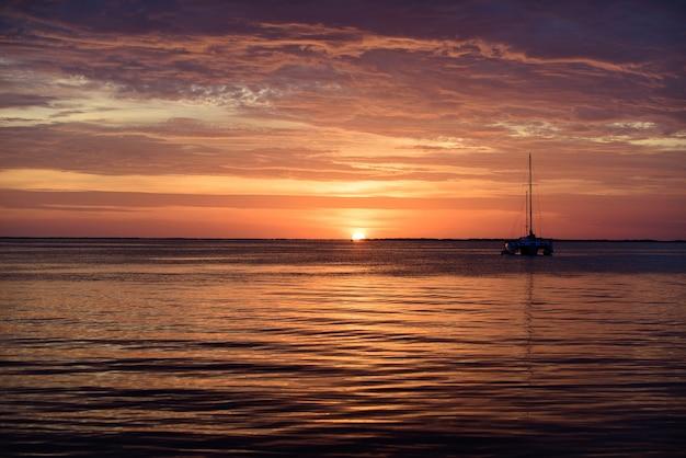 日没時の海のボート。水上を航行するオーシャンヨット。ヨット。