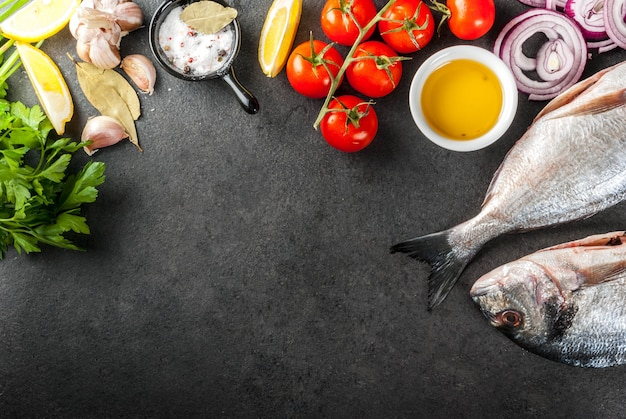Sea bream with ingredients for cooking on black stone table