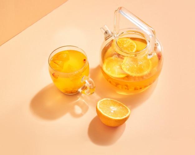 세련된 유리 주전자에 바다 갈매 나무속과 오렌지 음료.