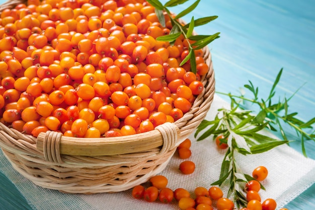 Sea buckthorn berry antioxidants useful for health with a branch in a basket on a wooden background, natural medicine, organic.