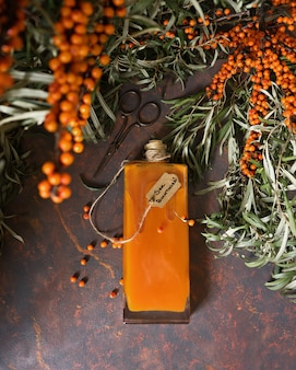 Sea buckthorn syrup in the glass vintage bottle and brunches of sea buckthorn