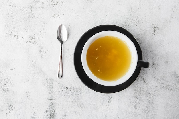 Sea buckthorn tea in dark cup isolated on bright marble background. overhead view, copy space. advertising for cafe menu. coffee shop menu. horizontal photo.