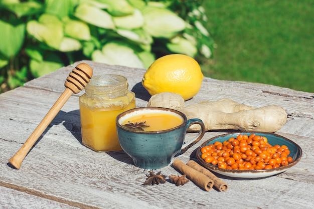 シーバックソーンティーハニーレモンと木製テーブルの生姜アンティコールドティーは健康のための抗酸化物質です