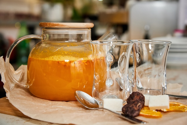 Облепиховый чай в прозрачном стеклянном чайнике