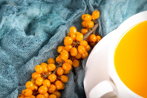 Sea-buckthorn tea in white cup with  berries with branch on natural green napkin