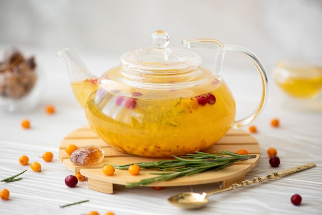 Sea buckthorn tea with lingonberry and rosemary in a glass teapot
