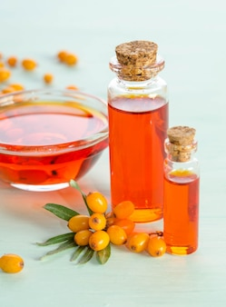 Sea buckthorn and two bottles, bowl with sea buckthorn oil