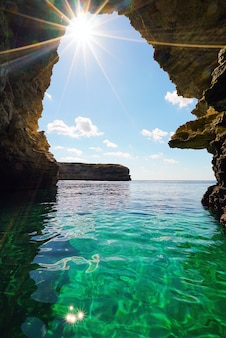 Sea cave in the rock with bright sunlight .