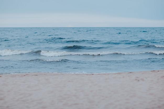 Морское побережье с голубой водой. штормовая погода на озере. песчаный пляж с волнами в плохую погоду.
