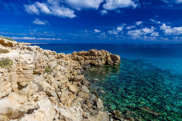 Sea coast with clear turquoise water, stone cape, blue sky with clouds.